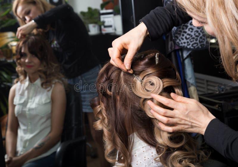 Мастерский стилизатор делает дизайн свадьбы невесты красивый удовлетворенный клиент в профессиональном салоне парикмахерских услу стоковые фото