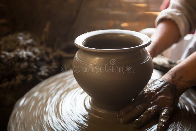 мастерство Конец-вверх рук работая глина на колесе гончара стоковые фото