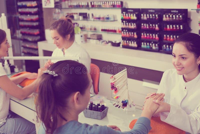 Мастеры ногтя выполняя маникюр стоковые фотографии rf