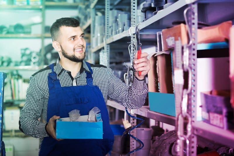 Мастер выбирает необходимые материалы и инструменты для ремонта стоковая фотография rf