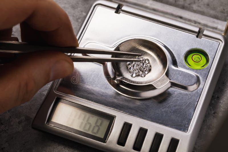 Мастер измеряет вес драгоценных камней в масштабах ювелирных изделий стоковое фото