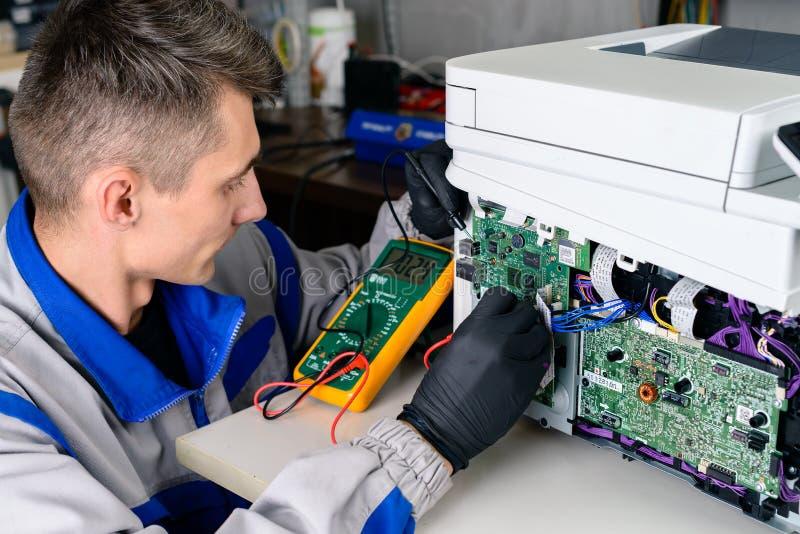 Мастер ищет повреждение, конторские машины ремонта использующ вольтамперомметр стоковая фотография rf