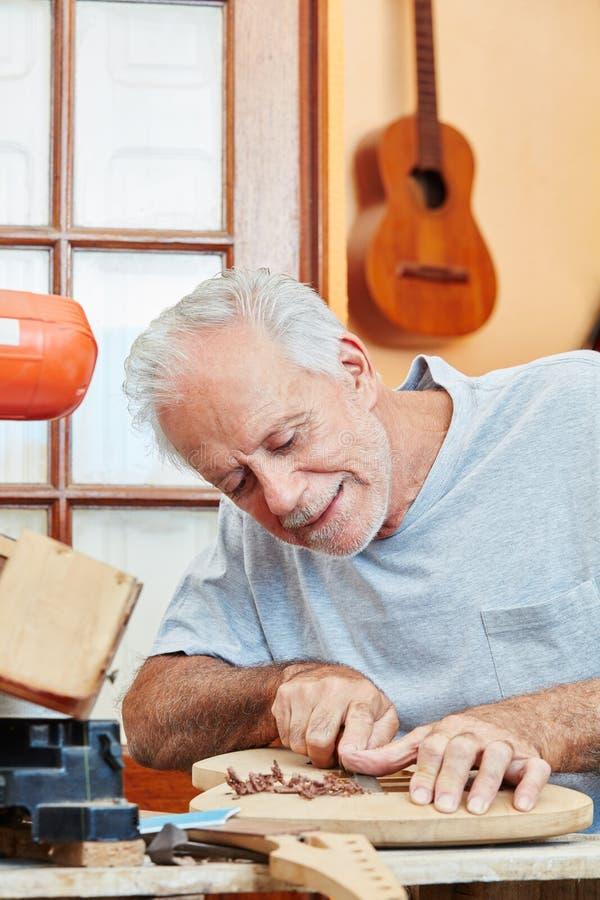 Мастер как создатель гитары работает с точностью стоковое изображение