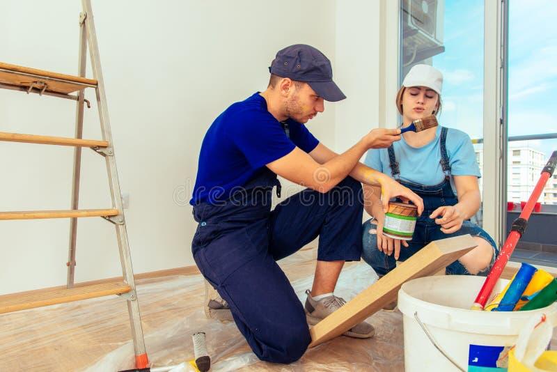 Мастер лакируя деревянную полку используя Paintbrush стоковые фото