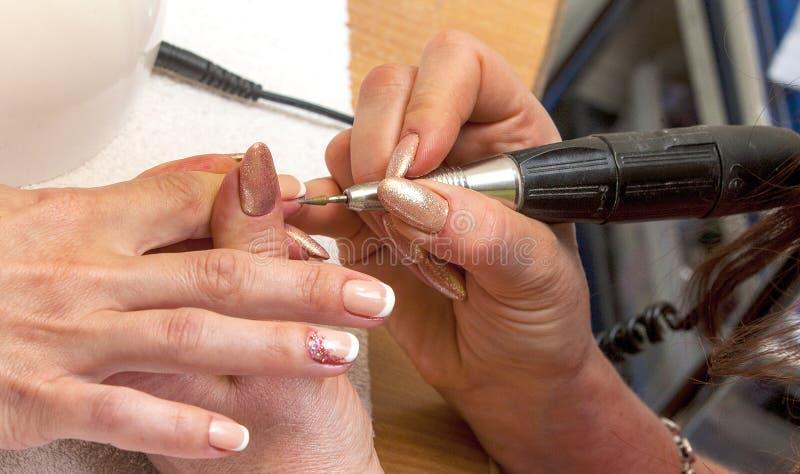 Мастер ногтя в резиновых перчатках делает маникюр стоковые фото