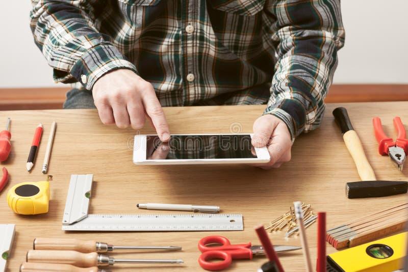 Мастер работая на проекте DIY с его таблеткой стоковое изображение rf