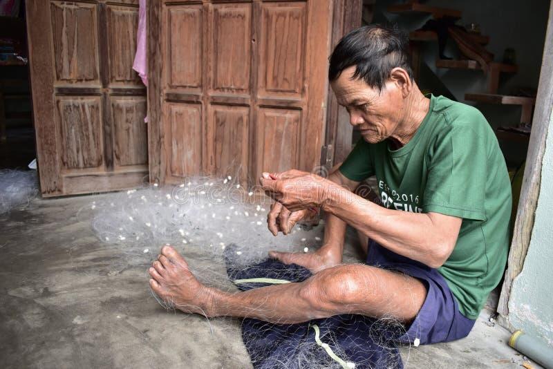 Мастер работая на рыболовной сети в въетнамской деревне стоковые фотографии rf