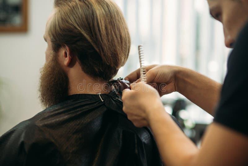 Мастер режет волосы и борода людей в парикмахерскае, парикмахера делает стиль причёсок для молодого человека стоковые изображения rf