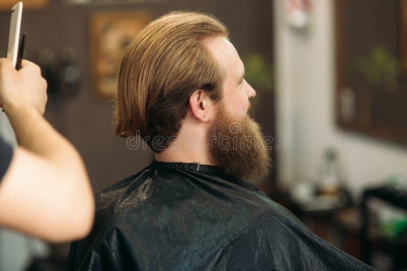 Мастер режет волосы и борода людей в парикмахерскае, парикмахера делает стиль причёсок для молодого человека стоковая фотография