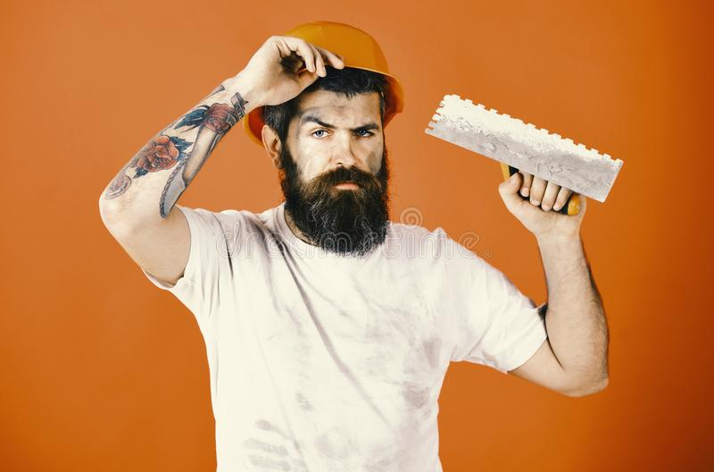 Мастер ремонтника штукатура в владениях шлема или трудной шляпы стоковое фото