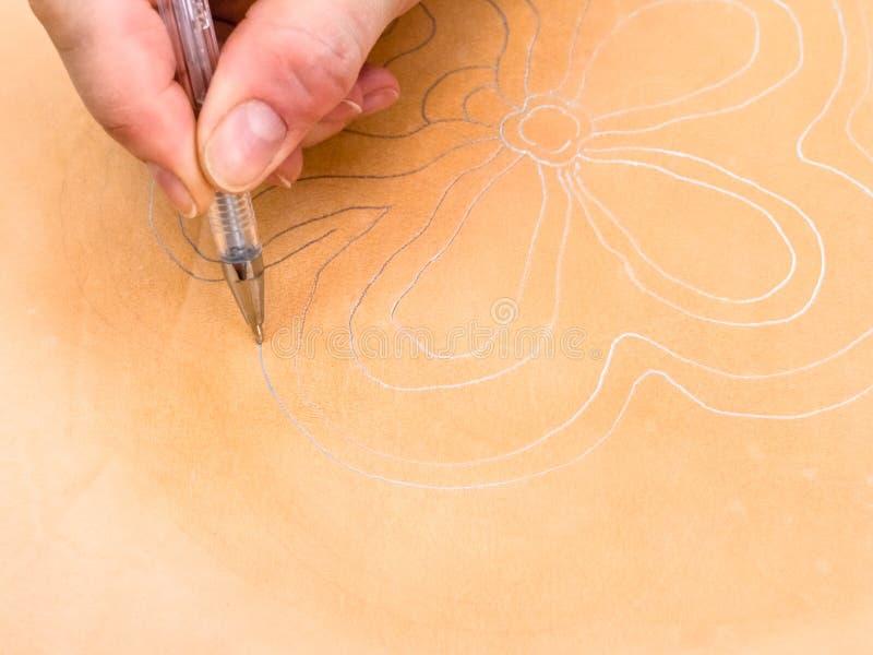 Мастер рисует цветочный узор на коже стоковые изображения