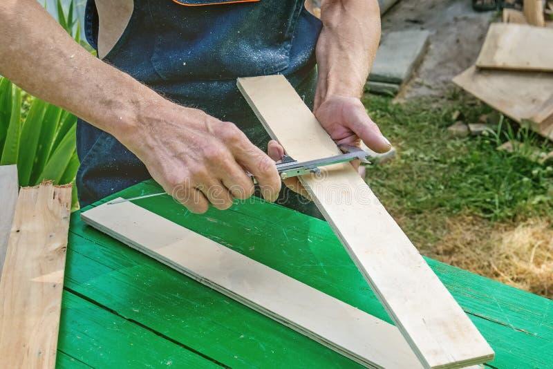 Мастер точит деревянную панель с электрическим точильщиком на солнечный день в саде dimensioning стоковое фото rf