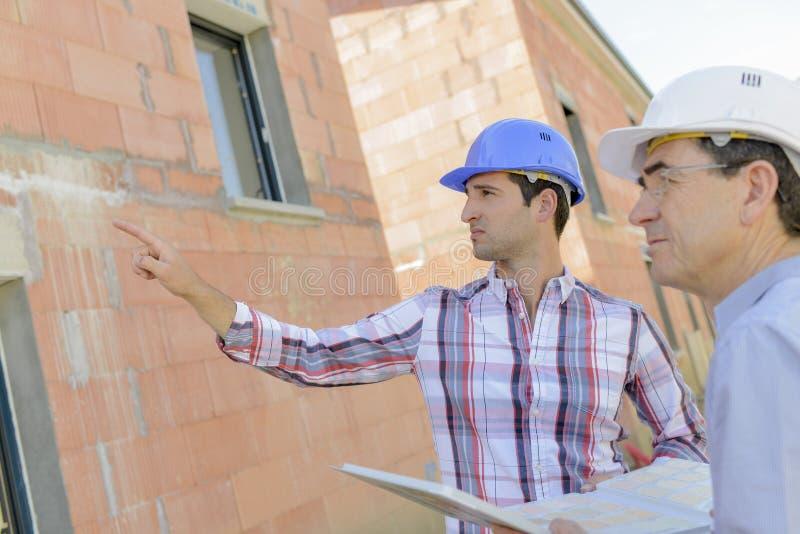 Мастер указывая на незаконченный дом стоковое изображение rf