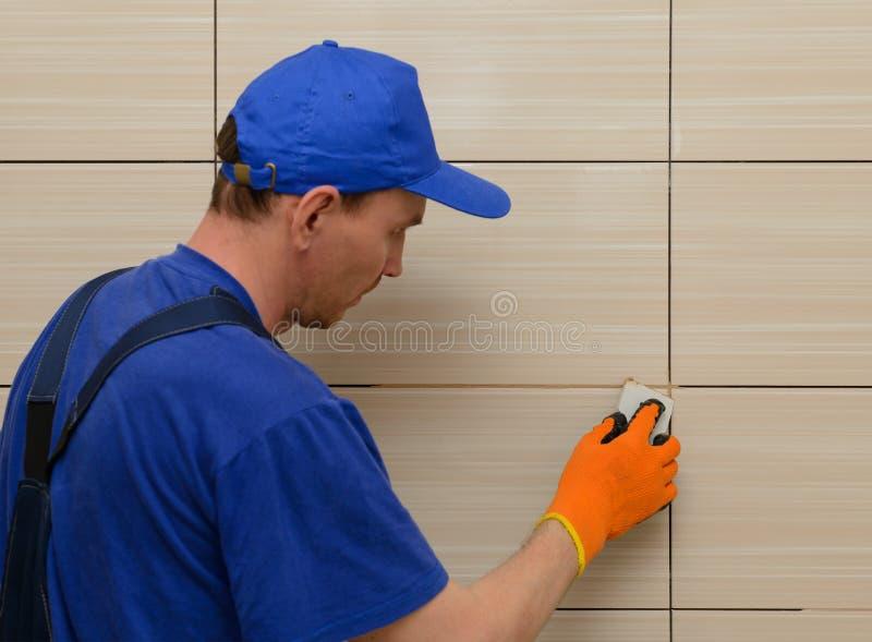 Мастер-tiler преграждает швы между плитками стоковая фотография