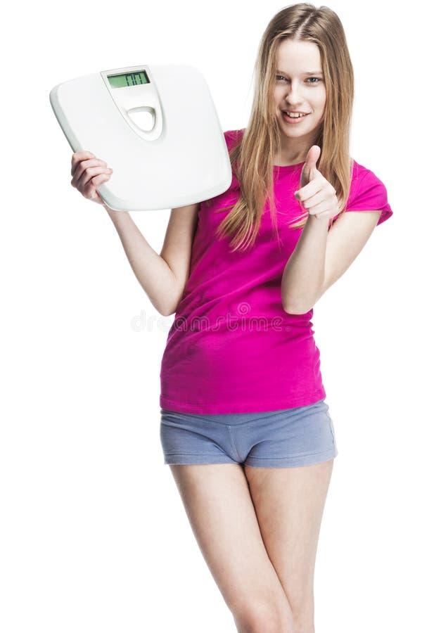 Масштабы молодой красивой белокурой девушки hplding стоковое изображение rf