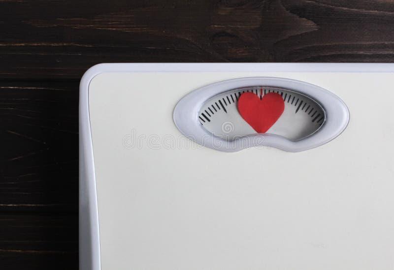Масштабы пола с сердцем вместо номеров Полюбите вашу концепцию тела Мотивация образа жизни фитнеса : стоковые изображения rf