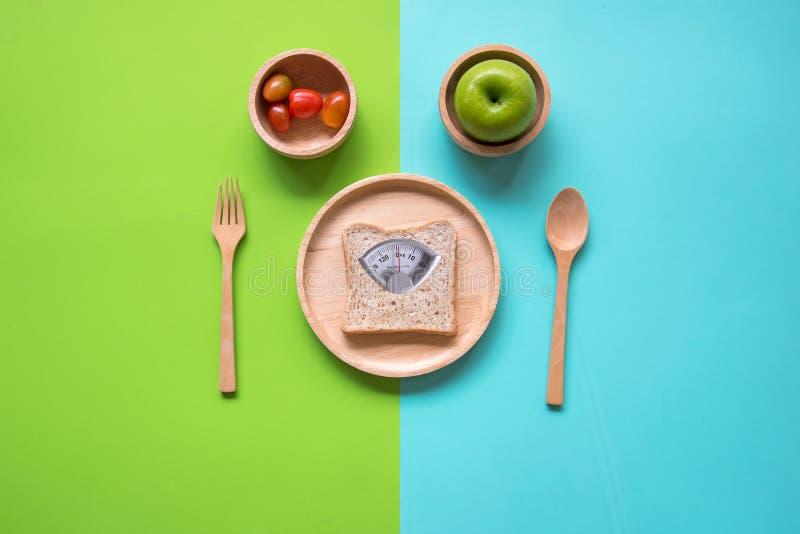 Масштаб веса с полезным куском хлеба и измеряя ленты на деревянной плите для уменьшения веса стоковые фотографии rf