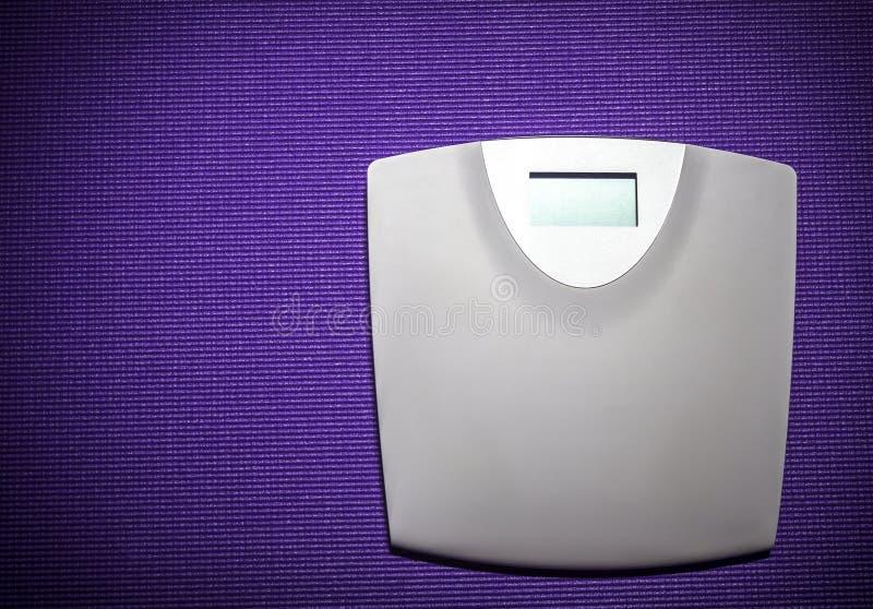 Масштаб веса цифров на фиолетовом ковре стоковая фотография