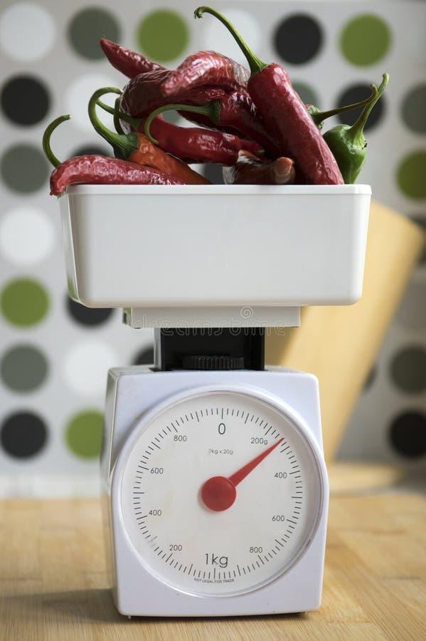Масштаб веса Kitchenware с перцами chili стоковые изображения