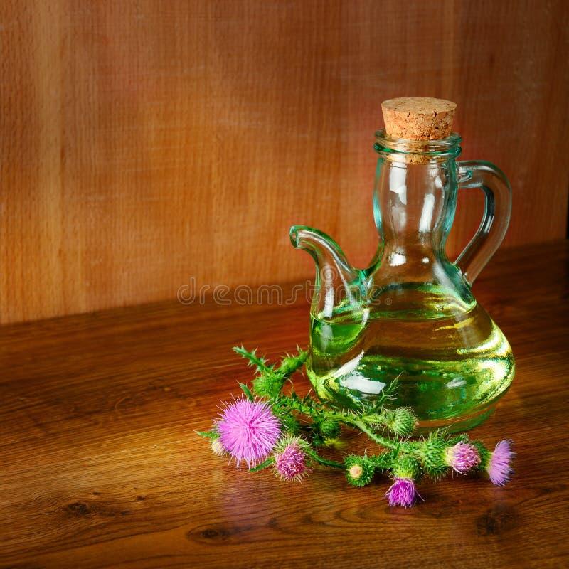 Масло и цветки thistle молока на деревянном стоковая фотография rf