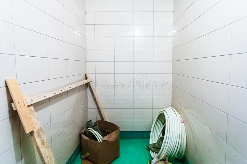 Материалы для паять для приспособлений ванной комнаты ремонтов или fitment ванной комнаты в комнате с плиткой квартира вниз стоковое фото rf