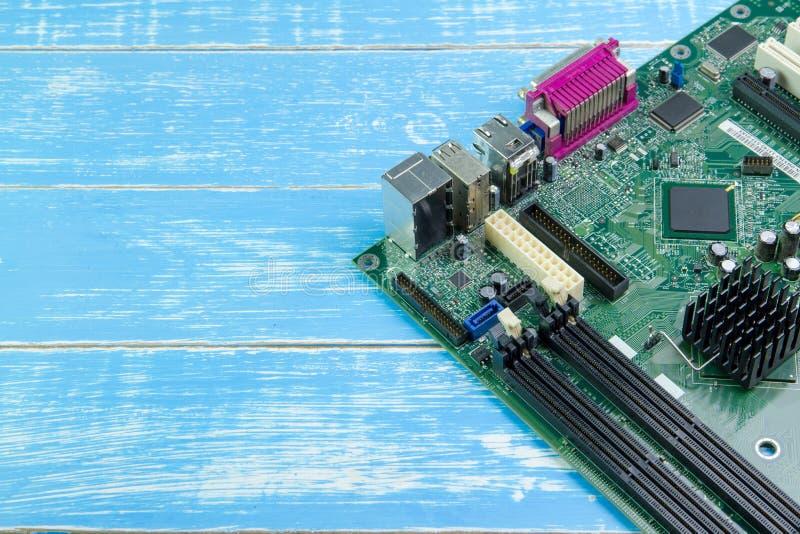 Материнская плата компьютера на голубой деревянной предпосылке стоковая фотография rf