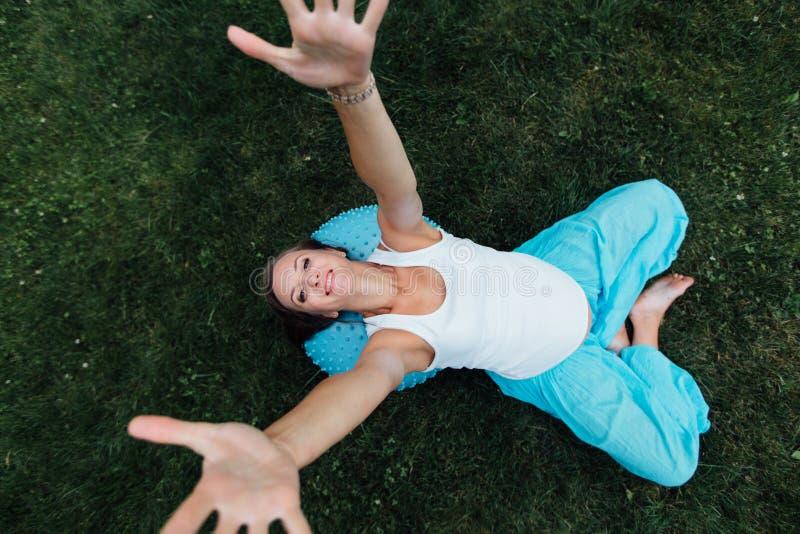 Материнство счастливой беременной йоги пренатальное делая различные тренировки с fitball в парке на траве, Pilates Взгляд сверху стоковое фото rf