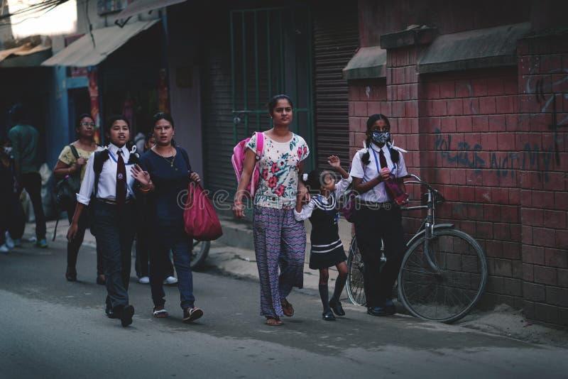Матери принимают ей детей к школе на улице Thamel стоковые изображения