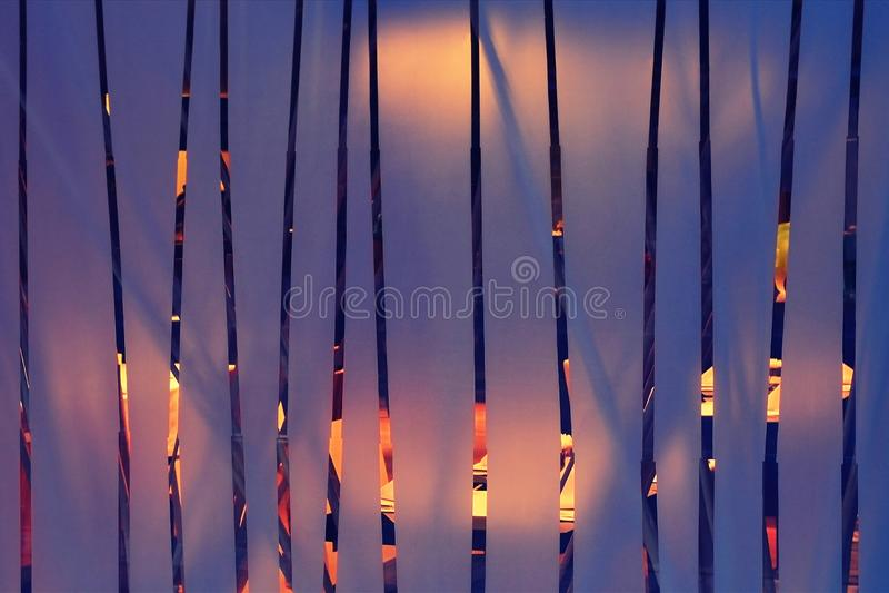 Матированное стекло с вертикальными прозрачными прокладками, за которыми освещенная зала, абстрактная внутренняя или внешняя пред стоковые фото