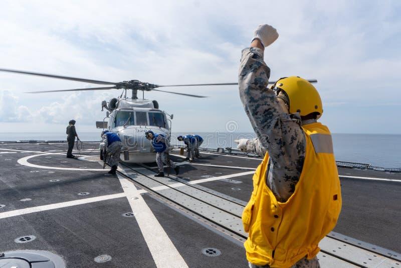 Матросы идут побелить мелом и приковать вертолет Sikorsky MH-60S Seahawk к кабине экипажа HTMS Bhumibol Adulyadej стоковая фотография
