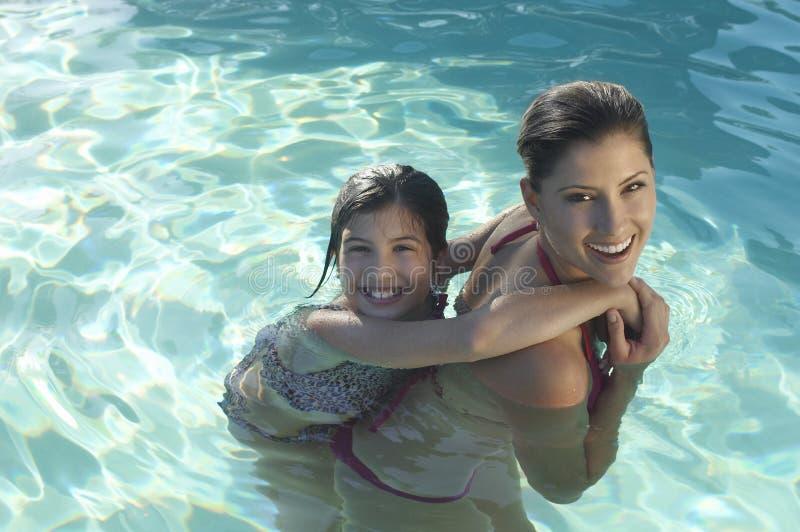 Мать давая автожелезнодорожные перевозки дочери в бассейне стоковые фотографии rf