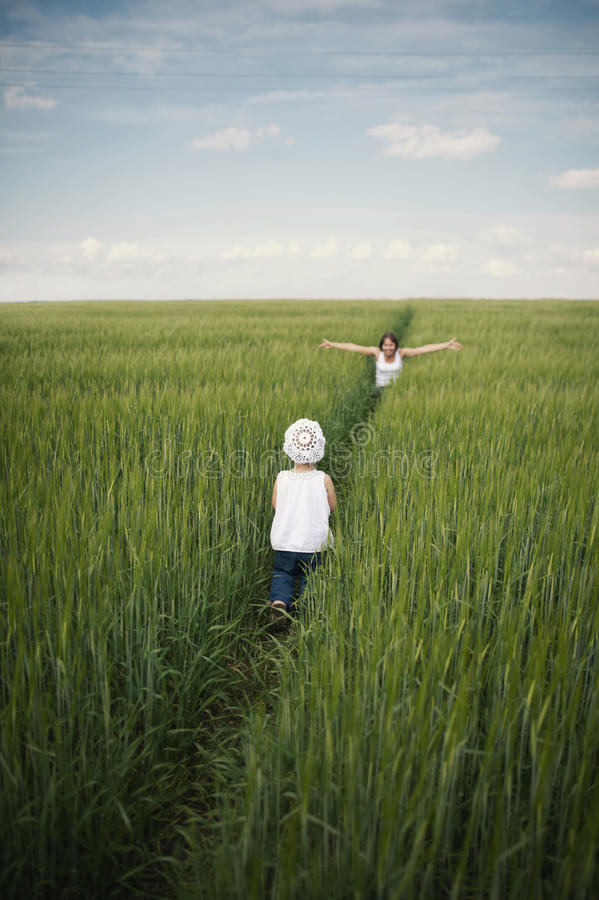 Мать встречая ее младенца в зеленом поле стоковые фотографии rf