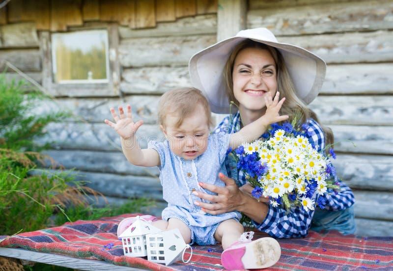 Мать в шляпе и пищать девушка ребенка в сельской местности стоковые фото