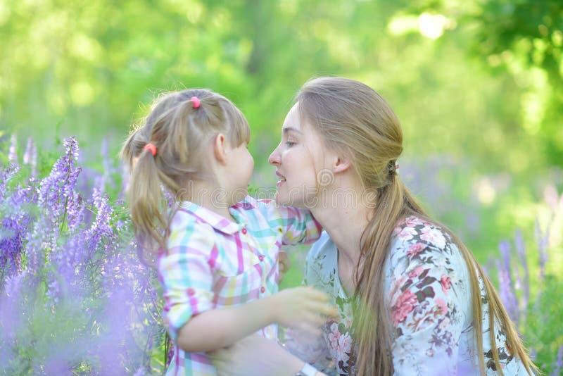 Мать говорит к дочери ребенка, играм, гримасничающ, смеясь стоковые фотографии rf