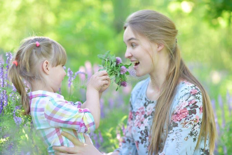 Мать говорит к дочери ребенка, играм, гримасничающ, смеясь стоковые фото