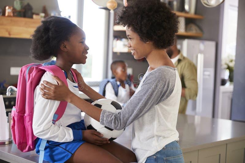 Мать говоря до свидания к дочери по мере того как она выходит для школы стоковые фотографии rf