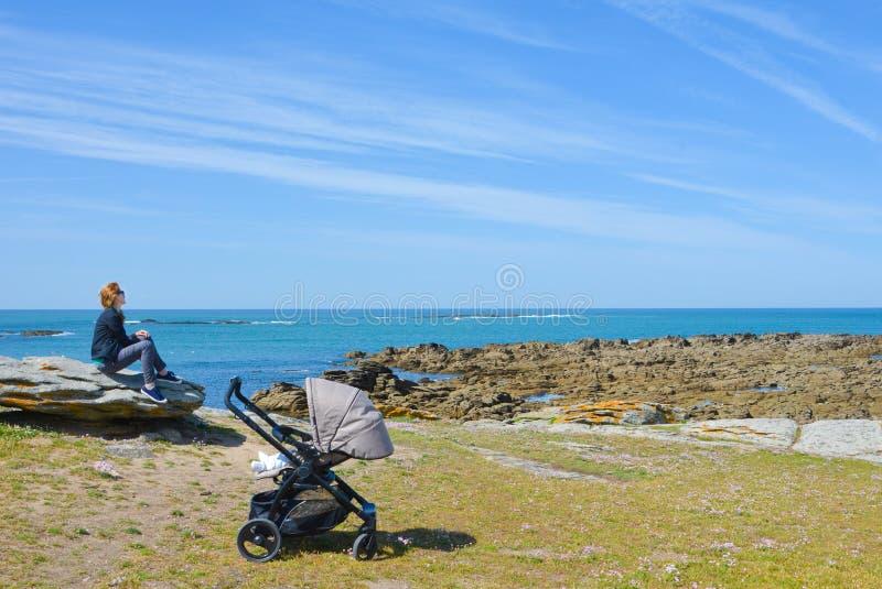 Мать гуляя с младенцем смотрит Атлантический океан стоковые изображения rf