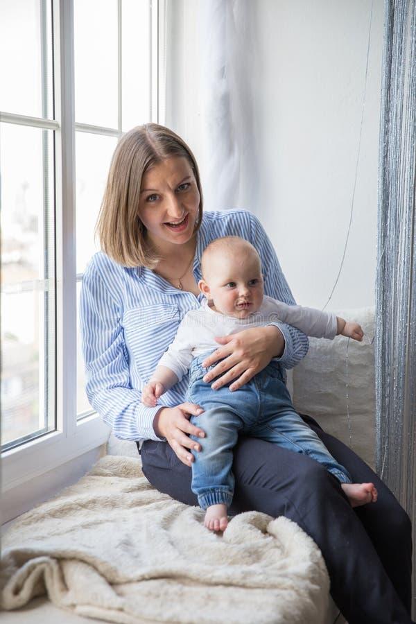 Мать держащ и обнимающ его дочь младенца стоковая фотография