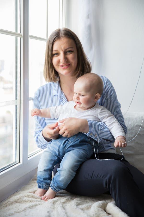 Мать держащ и обнимающ его дочь младенца стоковое изображение