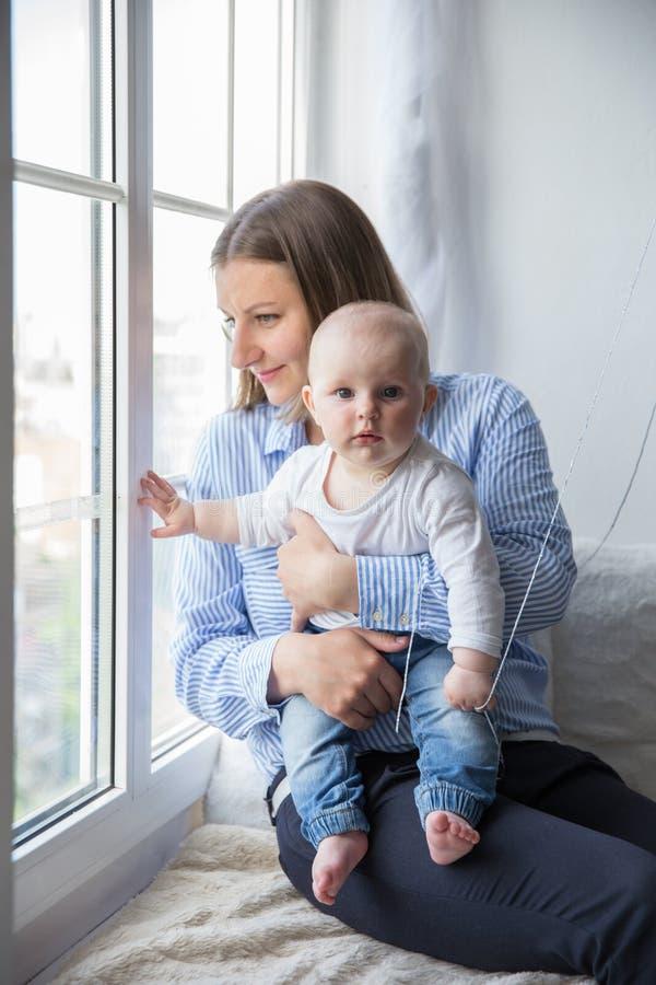 Мать держащ и обнимающ его дочь младенца стоковые фото
