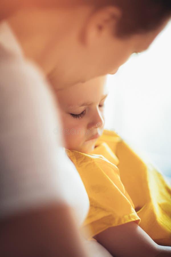 Мать держа к ее уснувшему маленькому сыну стоковые фотографии rf