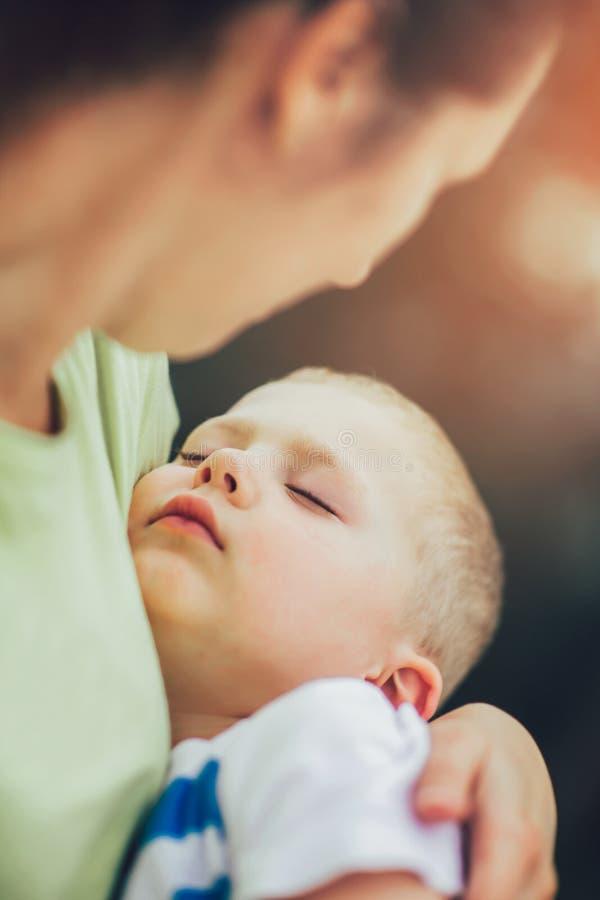 Мать держа к ее уснувшему маленькому сыну стоковая фотография rf