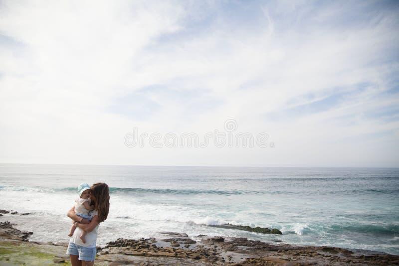 Мать держит своего ребенка перед морем в дневное время стоковая фотография rf