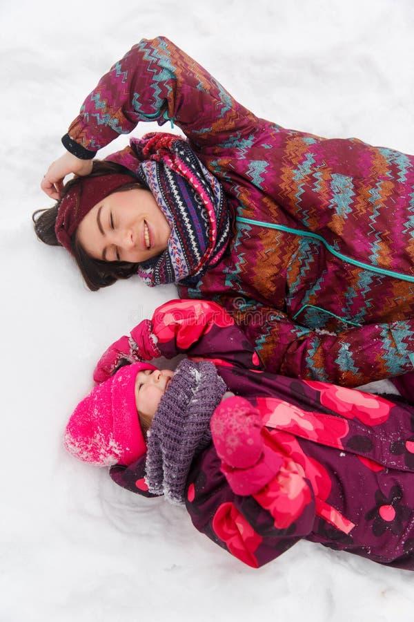 Мать, девушка лежа на снеге стоковое фото