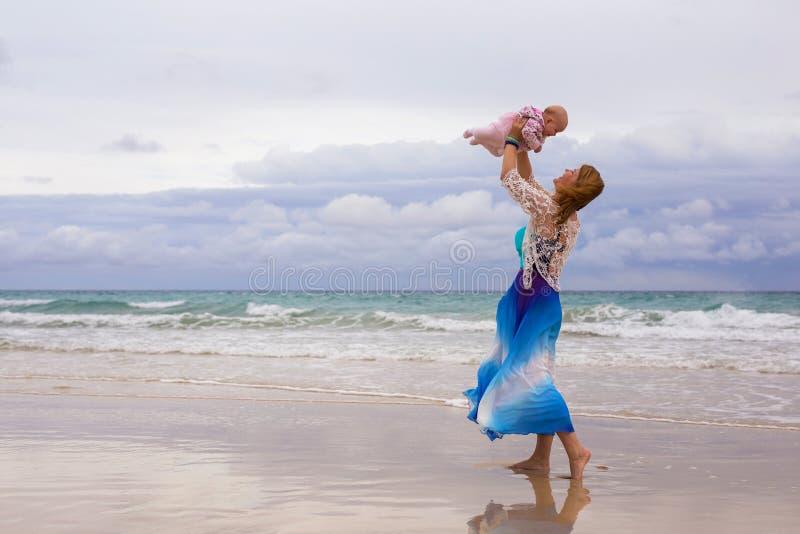 Мать держа ее младенца на пляже стоковая фотография