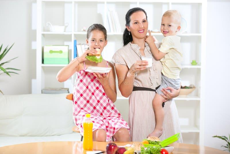 Мать делая завтрак для ее детей стоковое фото
