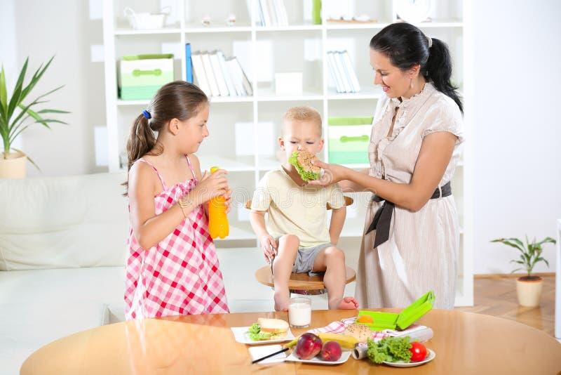 Мать делая завтрак для ее детей стоковая фотография