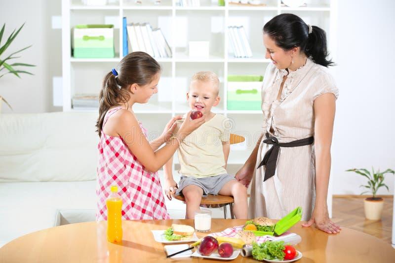 Мать делая завтрак для ее детей стоковое изображение