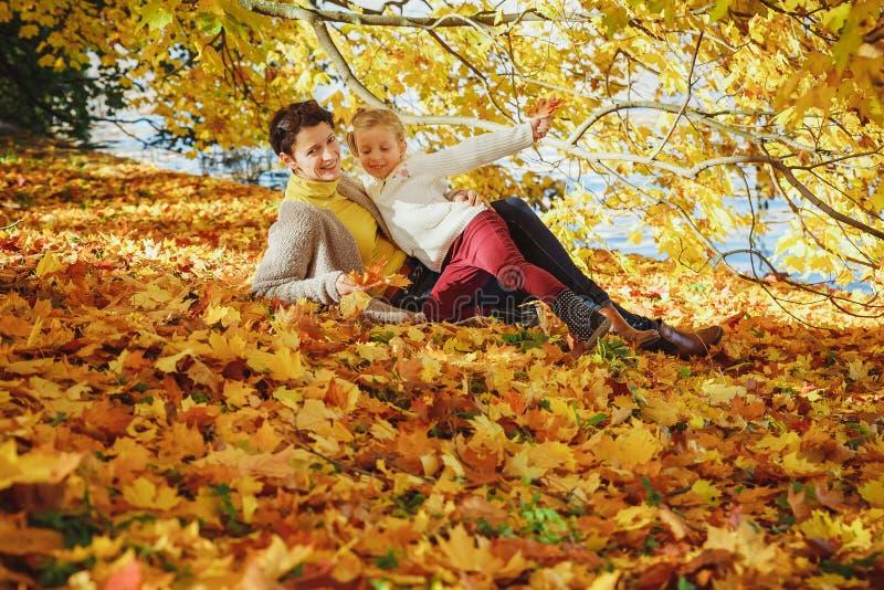 Мать играет со своей дочерью в осеннем парке Мама и ее ребенок, играющие вместе осенью, выходят на улицу Счастливого стоковое изображение rf
