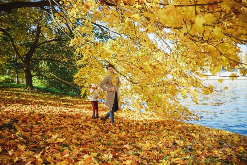 Мать играет со своей дочерью в осеннем парке Мама и ее ребенок, играющие вместе осенью, выходят на улицу Счастливого стоковые фотографии rf